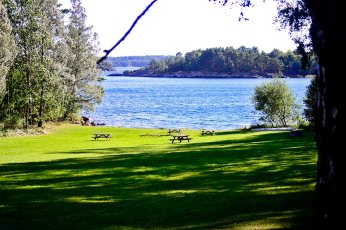 Panorámica césped mesas picnic mar archipiélago isla Grinda Suecia
