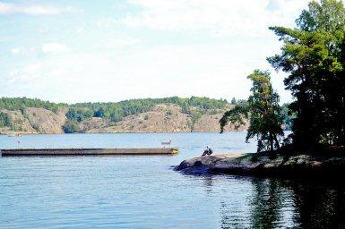 Hombre sentado rocas paisaje aguas archipiélago Fjaderholmarna Suecia