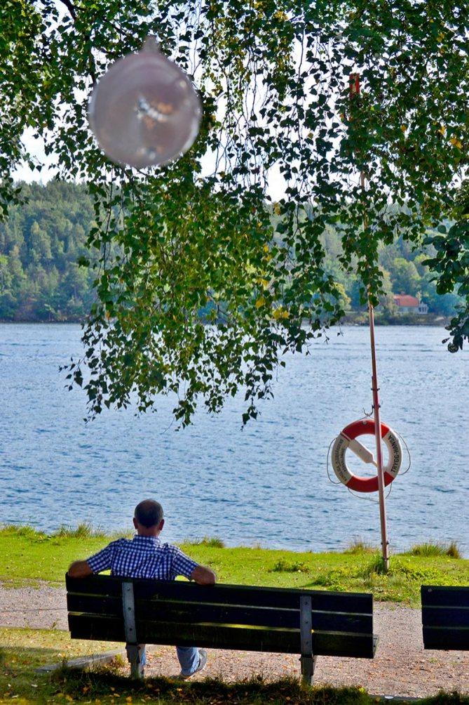 Salvavidas hombre banco mirando aguas archipiélago Estocolmo Fjaderholmarna Suencia