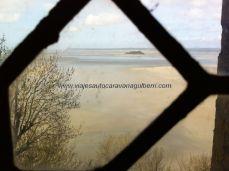 vista de la inmensa bahía mareal, con el molino en la isla que se divisa; en el centro puede verse una de las hileras de turistas que, acompañados de un guía, recorren la bahía en bajamar