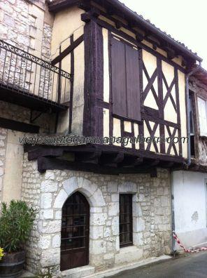 vivienda típica y cuidada: piedra en planta baja, con puerta arcada, y entramado de argamasa en planta superior