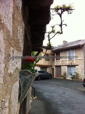 la casa de la derecha, en la placita, rompe la uniformidad de los entramados; la roja flor en su jarroncito perdona su atrevimiento
