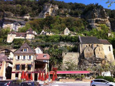 en primer término, el restaurante donde tomamos un tentempié, en su sombreada terraza; detrás, a su derecha, la pequeña iglesia