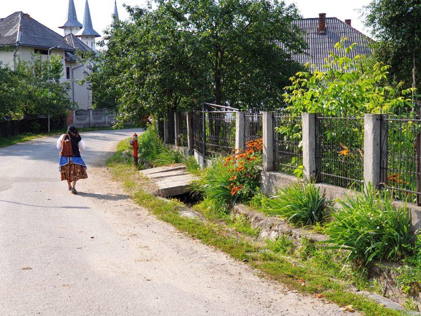 Mujer caminando en las afueras de la Iglesia de madera de Rogoz, Maramures (Rumanía)
