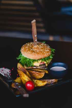 burger with fried fries on black plate with sauce on the side