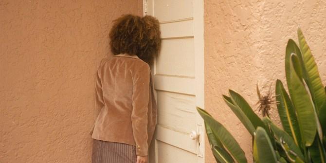 Vrouw op rug gezien tegen witte deur
