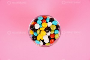 Chocolate coated peanuts in bowl on pink