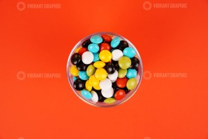 Chocolate drops in bowl on orange