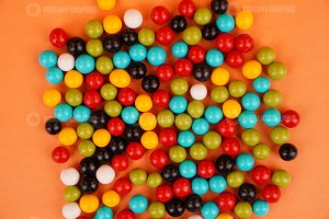 Colorful round dragee candies on orange background
