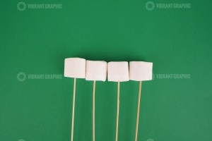Marshmallows with wooden sticks on green background