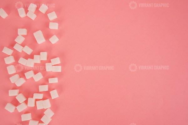 Lump sugar on bright pink stock image