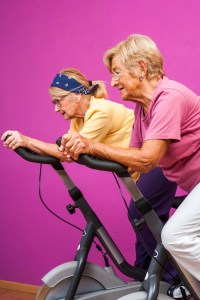 Senoir women doing spinning in gym