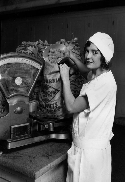 1920 model Nell Mckibbin weighs walnuts