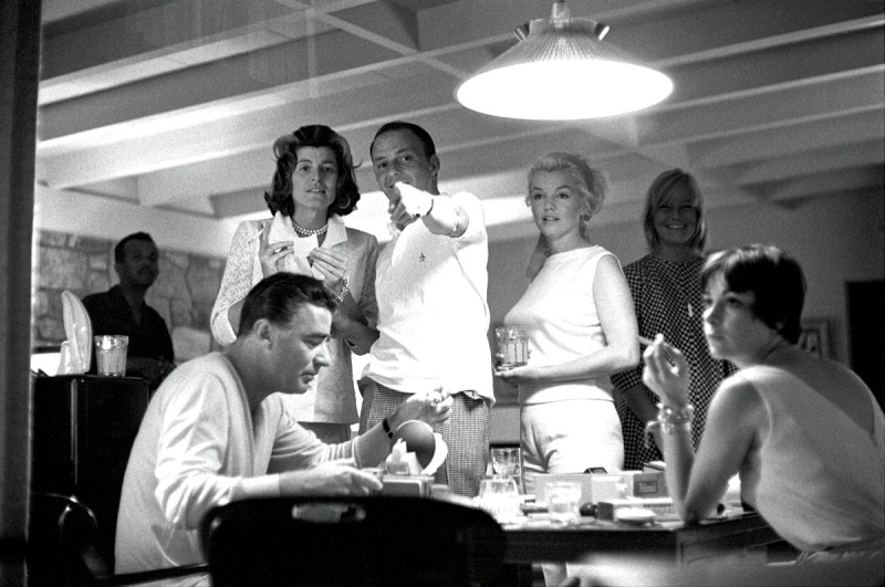 Frank Sinatra, Patricia Kennedy Lawford, Marilyn Monroe and Peter Lawford play with a new Polaroid camera (May Britt is in background). Photo by Bernie Abramson.