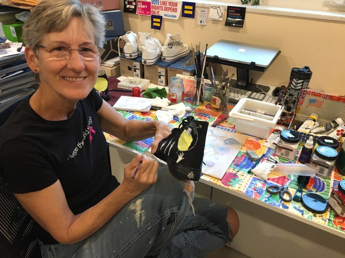 The artist, Vicki Rosenthal, is sitting at her desk painting a pair of shoes. She is a white woman with short dark blonde hair and wearing glasses. She is holding a black canvas hi-top sneaker in her left hand and a paint brush in her right hand. She is wearing a black short sleeve tee-shirt and blue jeans. On her desk there is lots of paints for her painting project.
