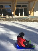 V sledging down the beginner slope after an exhausting day in ski school