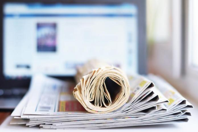 newspapers rolled up and screen media stock image