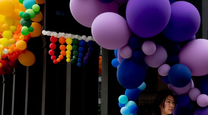 Balloons, flowers, lights, and other Pride decorations