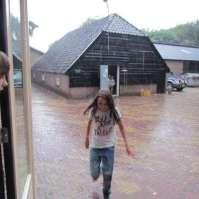 Eva rent in de regen snel over van de kleine schuur naar de eetzaal