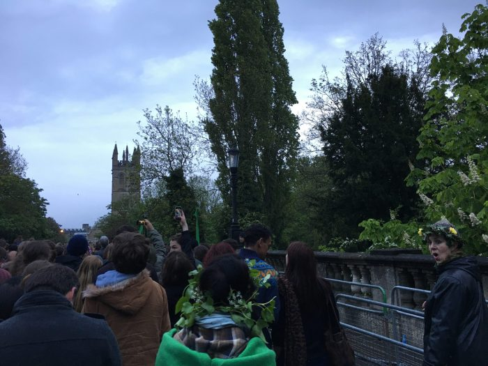 A crowd of people walk over a bridge. A woman is shouting to her friend, both wearing leafy headbands.