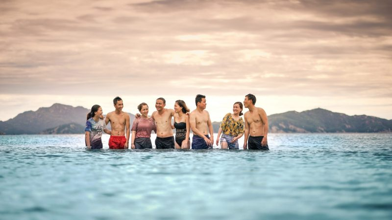Photo with a group of Asian men and women standing in water laughing