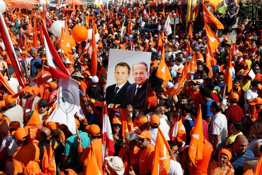 Supporters of the Free Patriotic Movement (FPM) carry flags and a picture of Christian politician and FPM founder Michel Aoun. (Reuters)