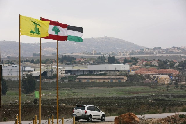 Flags of Hezbollah, Lebanon and Palestine are seen fluttering near the border with Israel in the village of Khiam, Lebanon, on December 4, 2018. (Reuters)