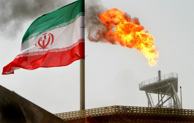 A gas flare on an oil production platform in the Soroush oil fields is seen alongside an Iranian flag in the Persian Gulf, Iran, July 25, 2005. (Reuters)