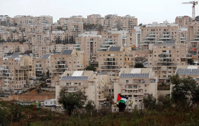 A demonstrator holds a Palestinian flag as the Jewish settlement of Modiin is seen in the background, during a protest against Trump's Middle East peace plan. (Reuters)