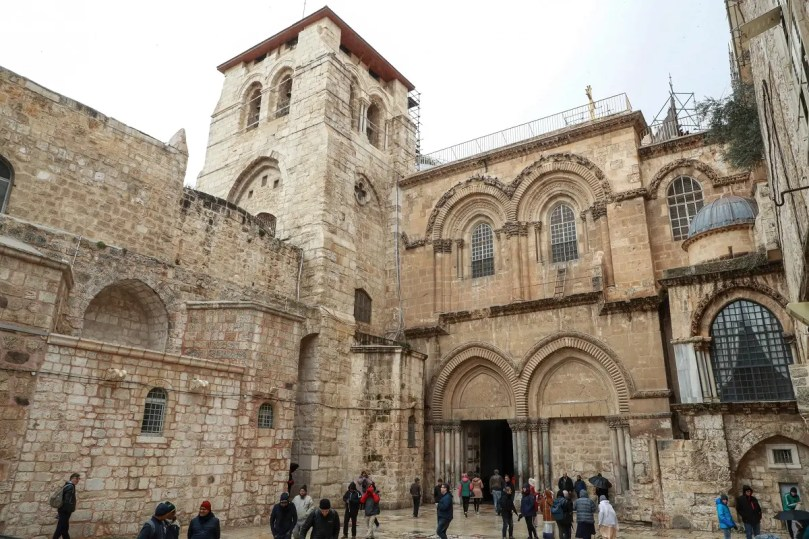 People walk outside the Church of the Holy Sepulchre in the Old City of Jerusalem on January 21, 2020. (AFP)