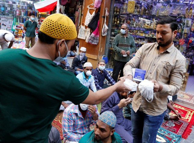 A vendor distributes protective face masks in Manama before restrictions on travel and businesses were imposed. (File photo: Reuters)