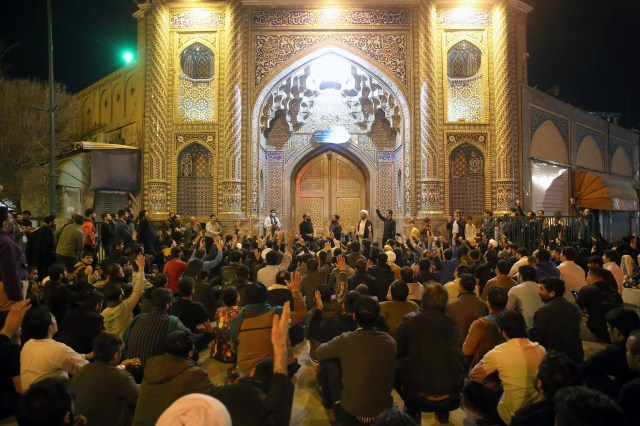 People gather outside the closed doors of the Fatima Masumeh shrine in Iran's holy city of Qom on March 16, 2020. (File photo: AFP)
