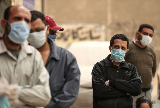 Egyptian men wearing masks wait outside a center of non-governmental organization Egyptian Food Bank to receive cartons with foodstuffs on April 05, 2020 in Cairo. (AFP)