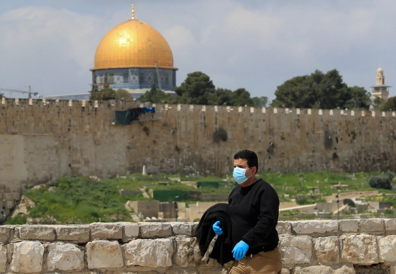 A man wearing a mask and gloves walks past the Dome of the Rock mosqu in Jerusalem's Old City on April 2, 2020. (AFP)