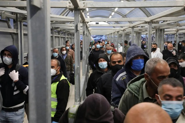 Palestinian laborers enter Israel through the Mitar checkpoint in the occupied West Bank city of Hebron, on May 3, 2020. (AFP)
