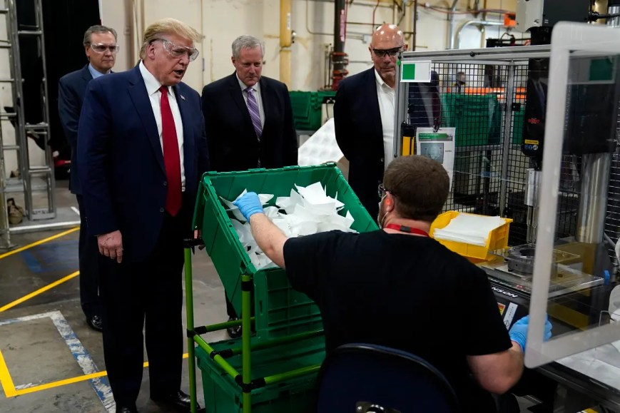 President Donald Trump participates in a tour of a Honeywell International plant that manufactures personal protective equipment, Tuesday, May 5, 2020, in Phoenix, with Tony Stallings, vice president of Integrated Supply Chain at Honeywell, right and White House chief of staff Mark Meadows. (AP)
