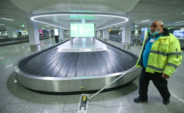 A staff member cleans the area near a baggage belt as the International airport presents additional safety measures, amid the coronavirus disease outbreak in Frankfurt, Germany, on May 12, 2020. (Reuters)