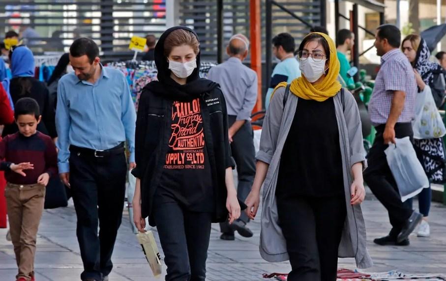 Iranians, some wearing face masks, walk along a street in the capital Tehran on June 3, 2020, amid the novel coronavirus pandemic crisis. (AFP)