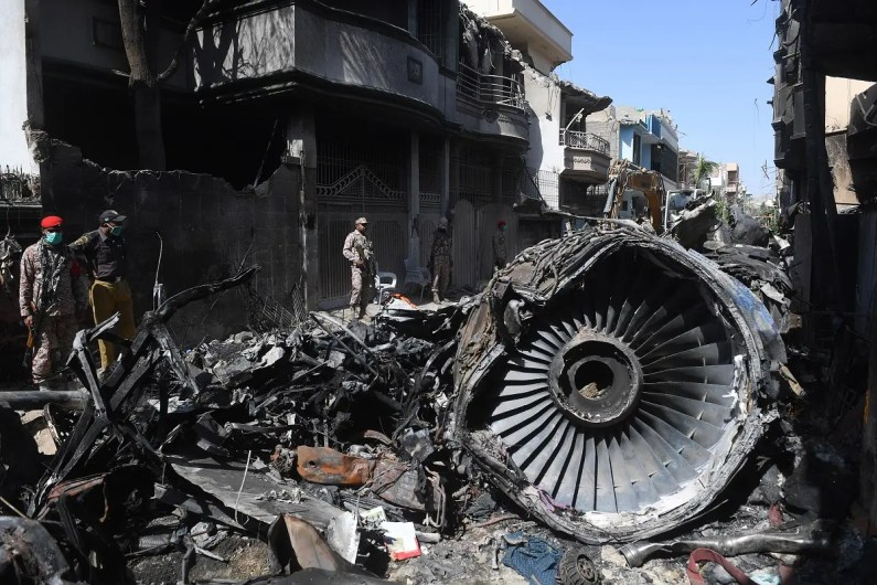 In this file photo taken on May 24, 2020, security personnel stand beside the wreckage of a plane at the site after a Pakistan International Airlines aircraft crashed in a residential area days before, in Karachi. (AFP)