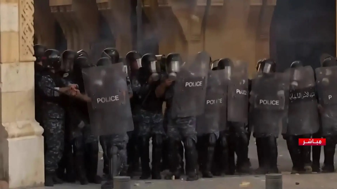 Lebanese police forces confront protesters near parliament. (Al Arabiya)