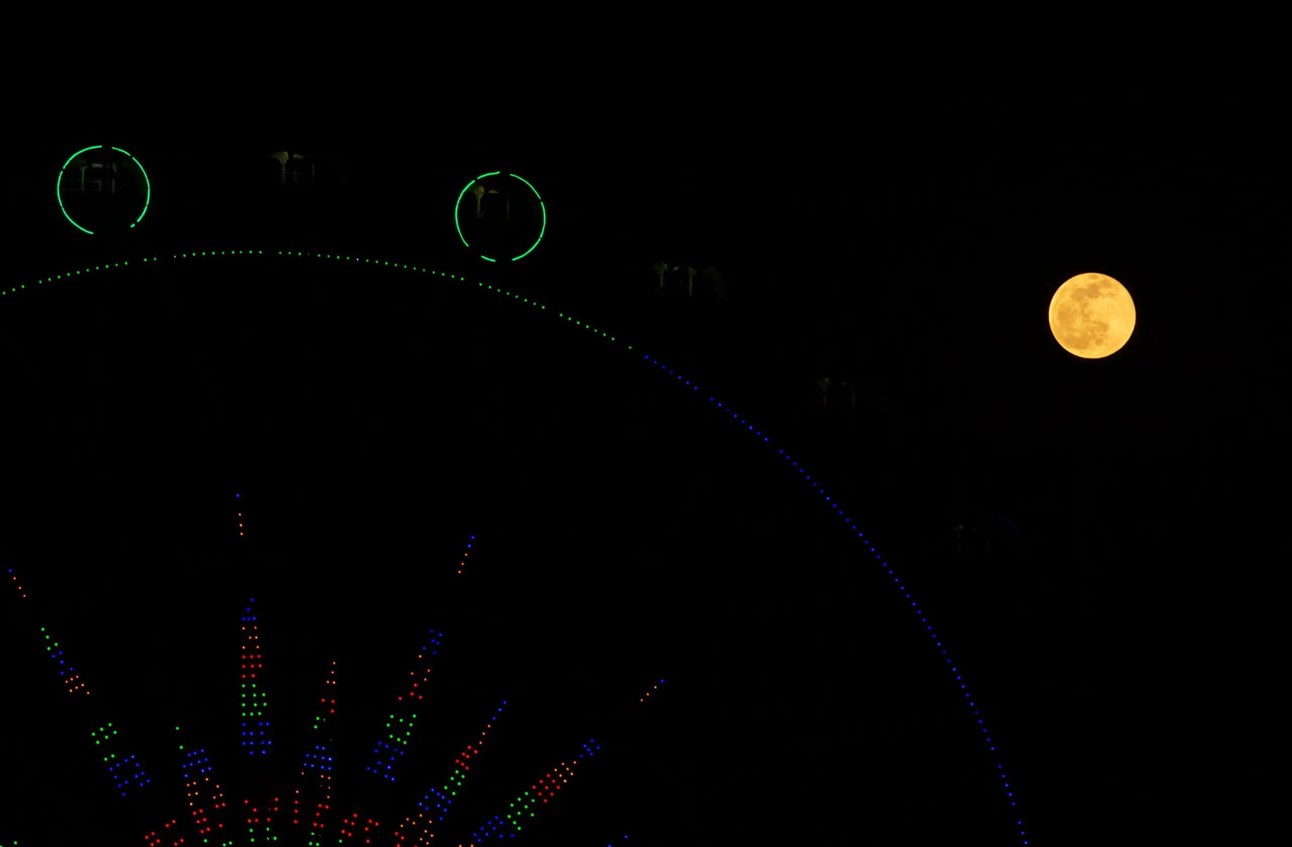 The full moon is pictured above a ferris wheel in the southern Iraq city of Basra on December 30, 2020. (AFP)