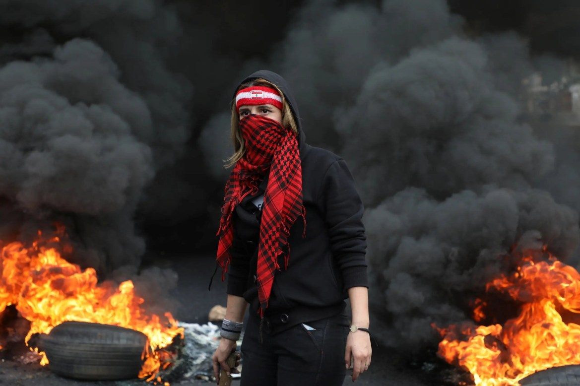 Demonstrators carry a tire to be set on fire during a protest against the fall in Lebanese pound currency and mounting economic hardships, in Zouk, Lebanon March 8, 2021. (Reuters)
