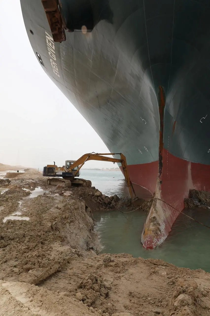 An excavator attempts to free stranded container ship Ever Given, one of the world's largest container ships, after it ran aground, in Suez Canal, Egypt March 25, 2021. (Reuters)