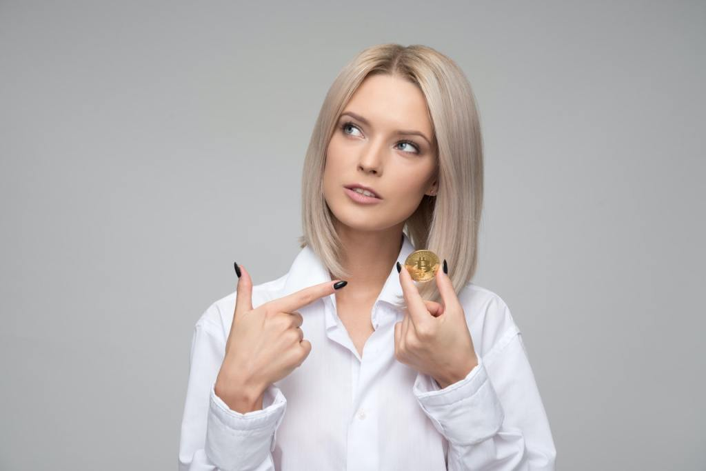Mulher apontando para dinheiro, uma moeda dourada.