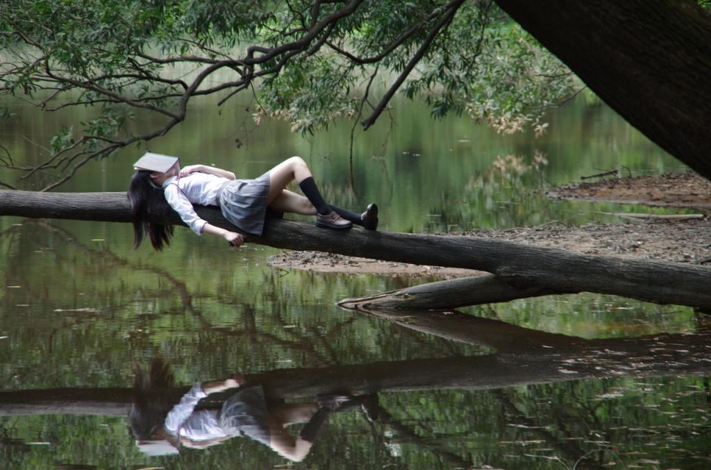 Mulher deitada na árvore com livre sobre o rosto.