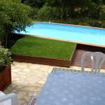 Inclassable. Dissimulation d'une machinerie piscine sous un carré de gazon synthétique incrusté dans une terrasse bois