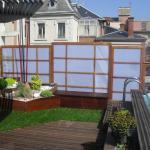 Piscine sur balcon avec terrasse bois gazon synthétique et occultation bois