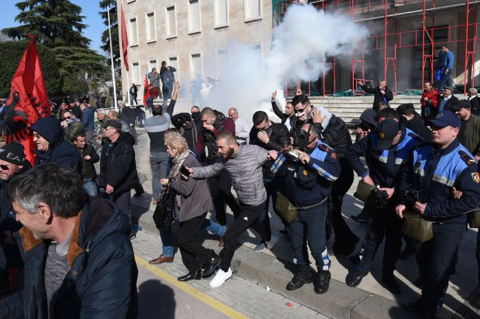 Protestors run from tear gas in Tirana, Albania during February protests calling for the resignation of the prime minister over corruption allegations.