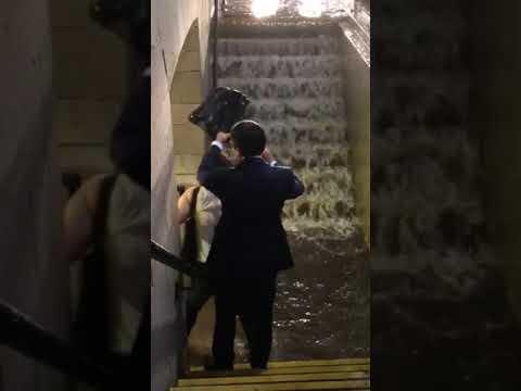 مشهد غريب .. أمريكية تحمل رجلاً حتى لا يبتل حذاؤه في المطر