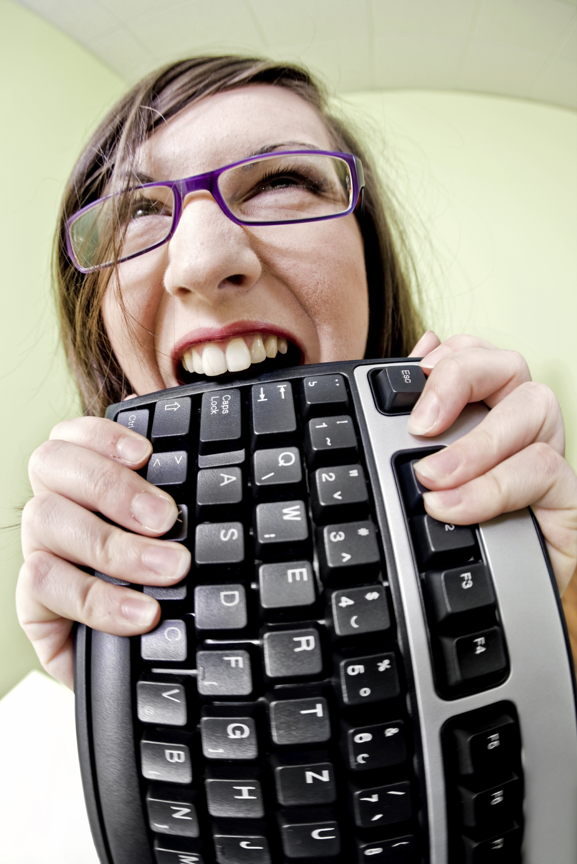 Frustrated computer user gnawing on keyboard.